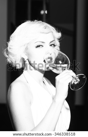 Closeup portrait of one attractive sensual smiling sexy young retro woman with blonde hair bright lips in dress in monroe style indoor drinking glass of wine black and white, vertical picture