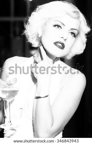 Closeup portrait of one attractive sensual smiling sexy young retro woman with blonde hair bright lips in dress in monroe style indoor with glass of wine black and white, vertical picture
