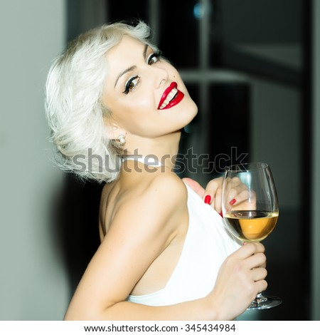 Closeup portrait of one attractive sensual smiling sexy young retro woman with blonde hair red lips in white dress in monroe style indoor with glass of wine on blurred background, square picture - stock photo