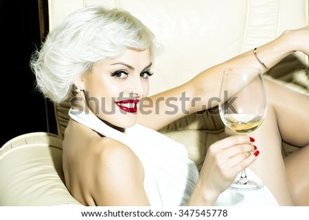 Closeup portrait of one attractive sensual smiling sexy young retro woman with blonde hair red lips in white dress in monroe style indoor drinking glass of wine sitting in chair, horizontal picture