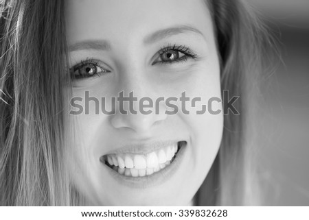 Closeup portrait of one beautiful happy smiling blonde young woman with long hair outdoor looking forward on blurred background black and white, horizontal picture - stock photo