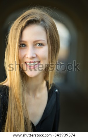 Closeup portrait of one beautiful happy smiling blonde young woman with long hair outdoor looking forward on blurred background, vertical picture
