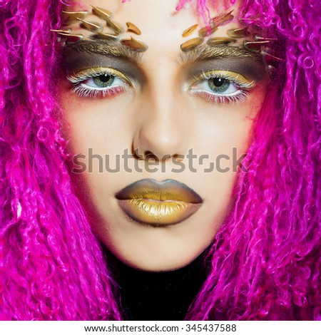 Closeup portrait of one beautiful wild young woman with bright golden animal monkey makeup with thorns on face in fur violet wig in studio, square picture