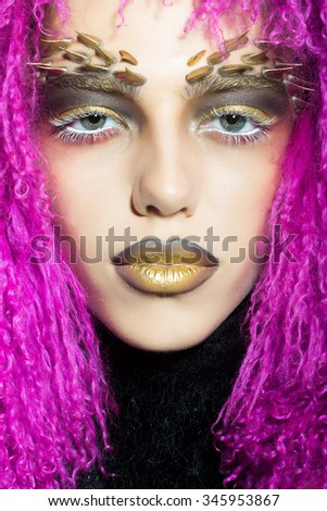 Closeup portrait of one beautiful wild young woman with bright golden animal monkey makeup with thorns on face in fur violet wig in studio, vertical picture