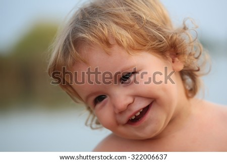 Closeup portrait of one cute funny playful happy emotional smiling little boy with blonde curly hair and round cheeks looking away outdoor on natural background, horizontal picture