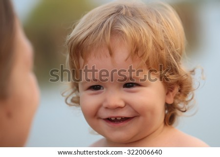 Closeup portrait of one cute funny playful happy smiling little boy with blonde curly hair and round cheeks looking on mother outdoor on natural background, horizontal picture - stock photo