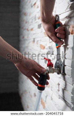 Closeup portrait of plumbers hands mounting a flexible pipe to a tap with adjustable spanner (monkey wrench) on grey stone wall  - stock photo