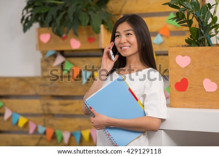 Closeup portrait of pretty Asian student communicating over mobile or smart phone, holding documents while waiting for her classmates or classmates in library, collage or university. - stock photo