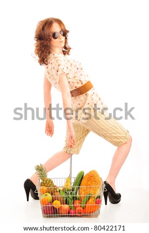 Closeup portrait of pretty caucasian woman wearing stylish clothes and sunglasses with shopping basket full of fresh vegetables, fruits, bread and other grocery products isolated on white background