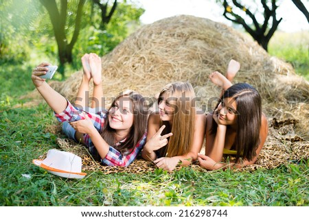 closeup portrait of 3 pretty girls having fun relaxing lying on hay happy smiling with excellent white teeth making selfie & looking at mobile phone on green summer outdoors copy space background - stock photo