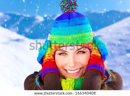 Closeup portrait of pretty woman closing ears from frosty wind, wearing colorful wool hat and gloves, spending winter holidays in the mountains - stock photo