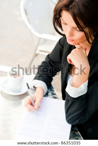 Closeup portrait of pretty woman sitting at cafe and signing documents while drinking her coffee. Natural light Outdoors - stock photo