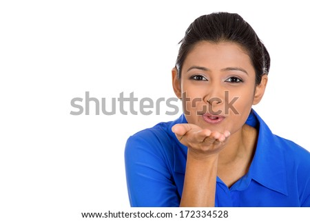Closeup portrait of pretty young woman puckering up lips to blow kiss at you camera gesture, isolated on white background. Positive emotion facial expression feeling, sign symbol body language
