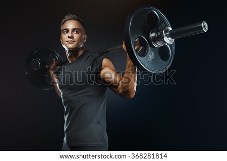 Closeup portrait of professional bodybuilder workout with barbell on black background. Muscular man training squats with barbells over head - stock photo