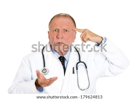 Closeup portrait of puzzled, confused senior doctor, old health care professional gesturing with finger against temple, asking question are you crazy? isolated on white background. Emotion, expression