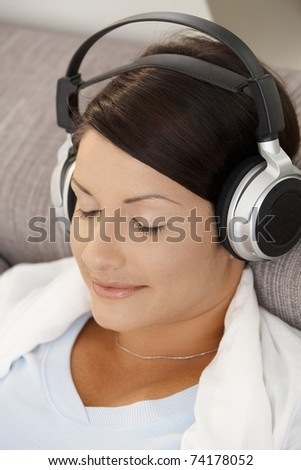 Closeup portrait of relaxed woman listening music on sofa with closed eyes.?