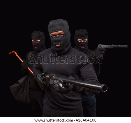 Closeup portrait of robber posing with rifle over black background with his partners. Studio shot of muscular men with weapons. Isolated on black. - stock photo