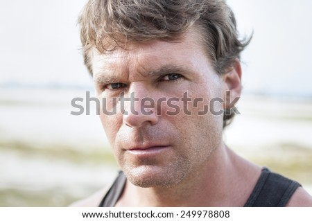 Closeup portrait of rugged Caucasian man with stern bold facial expression, distinct features, and intense predator eyes in undefined outdoor environment - stock photo