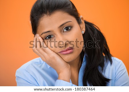 Closeup portrait of sad, depressed, stressed, thoughtful young woman, full of worries, looking at you, isolated on orange background. Human face expressions, emotions, feelings, reaction, attitude - stock photo