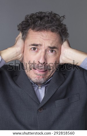 Closeup portrait of scared 40's businessman with curly grey hair covering closed ears to avoid listening management noise - stock photo