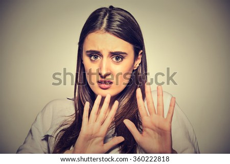 Closeup portrait of scared woman raising hands up in defense afraid about to be attacked or avoiding unpleasant situation, isolated on gray background. Negative human emotion facial expression feeling - stock photo