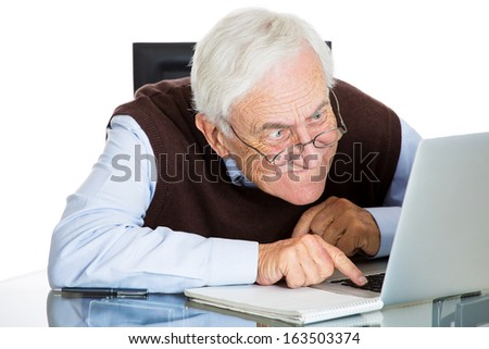 Closeup portrait of senior elderly mature man with glasses having eyesight problems trying to type on laptop, isolated on white background. Human emotions and facial expressions. Age related changes. - stock photo