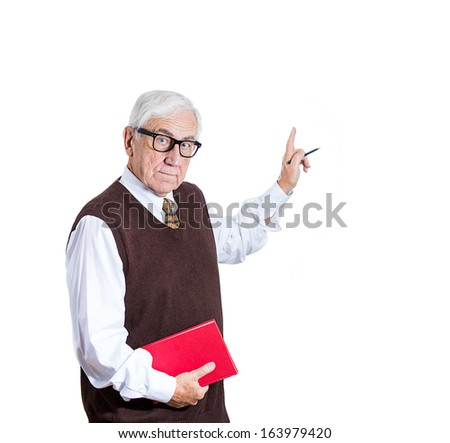 Closeup portrait of senior elderly teacher holding book and pen, looking very serious, pointing at a copy space, isolated on white background. Human emotions and facial expressions. Education concept - stock photo