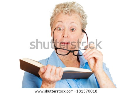 Closeup portrait of senior female, mature woman, old lady with trouble, problems reading book having bad vision, isolated white background. Emotions, facial expressions. Geriatric aging health issues - stock photo