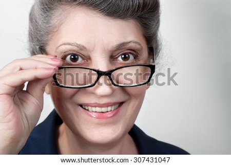 Closeup portrait of senior lady wearing glasses, smiling at camera