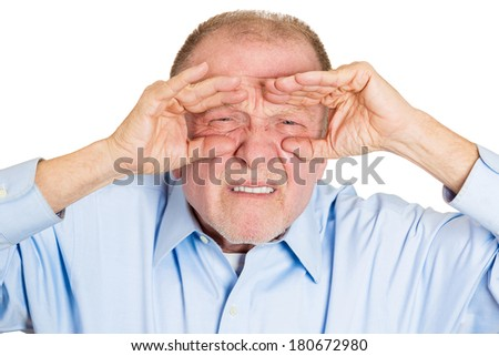Closeup portrait of senior mature curious man, looking through his fingers like binoculars, searching for something, unhappy disgusted with what is waiting in the future, isolated on white background - stock photo