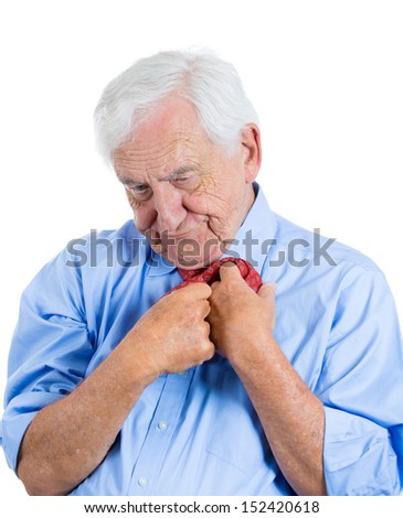 Closeup portrait of senior mature, elderly man very nervous, stressed, anxious, thinking about something making him crazy while fumbling with his tie, isolated on white background  - stock photo