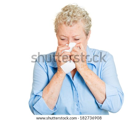 Closeup portrait of senior mature woman, miserable, sick with allergy, cold, blowing her nose with paper tissue, isolated white background. Human face expressions. Flu season, vaccination, prevention. - stock photo