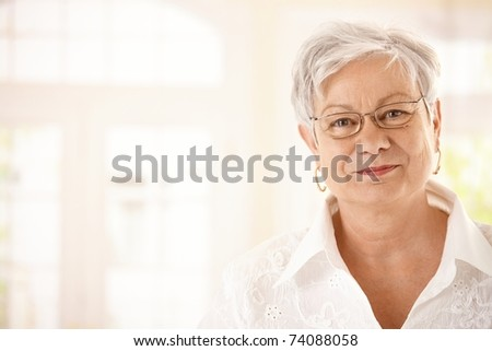 Closeup portrait of senior woman with glasses, looking at camera, smiling. - stock photo
