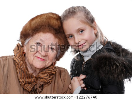 Closeup portrait of senior woman with little granddaughter in winter outwear on white background