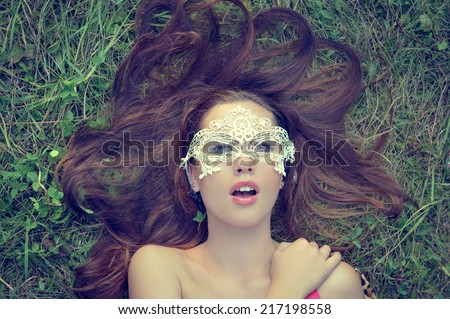 closeup portrait of sensual beautiful brunette young lady having fun wearing mask relaxing lying on green grass copy space background - stock photo