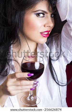 Closeup portrait of sensual brunette young woman in man's shirt holding a glass of wine in the bedroom