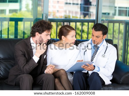Closeup portrait of serious health care professional or doctor or nurse showing explaining results of test to worried young couple on black couch in office, isolated on city urban background - stock photo