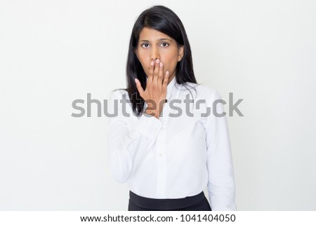 Closeup portrait of serious young pretty Indian business woman looking at camera and covering mouth. Secret concept. Isolated front view on white background.