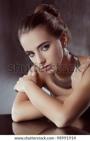 closeup portrait  of seriously brunette woman wearing silver jewellry, toned photo