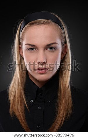 Closeup portrait of severe teenage girl wearing black, looking at camera.?