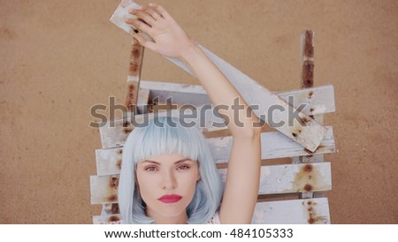 Closeup portrait of sexy beautiful woman in modern futuristic style posing on the damaged wooden blue sunbed. Creative look of woman on the beach wearing bikini and blue wig