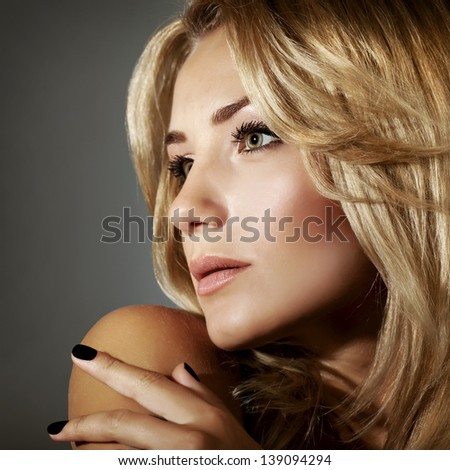 Closeup portrait of sexy blond woman isolated on gray background, fashionable hairstyle, perfect makeup, beauty concept