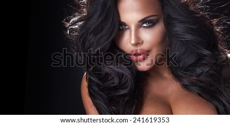 Closeup portrait of sexy brunette woman over black background.