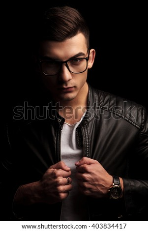 closeup portrait of sexy dark haired man wearing glasses, pulling his black leather jacket and looking at the camera in isolated black studio background