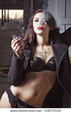 Closeup portrait of sexy smoking young girl in black underwear and coat - stock photo