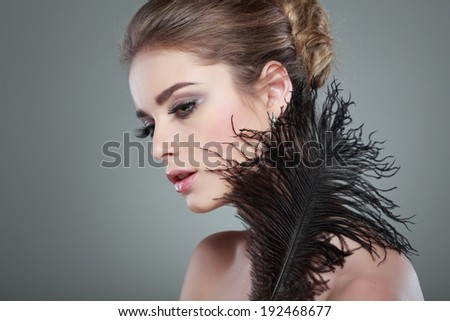 Closeup portrait of sexy whiteheaded young woman with black feather  on grey  background