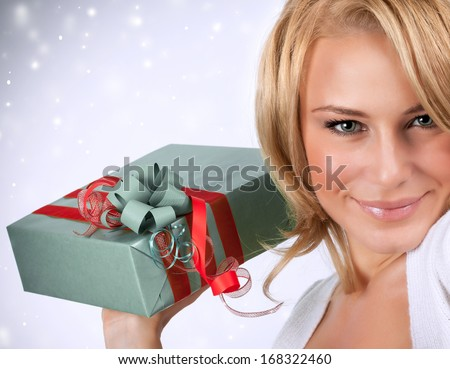 Closeup portrait of sexy woman holding in hands gray gift box with red ribbon, Christmas surprise, getting present concept
