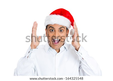 Closeup portrait of shocked and surprised handsome young man wearing red santa claus hat, hands in air, mouth eyes wide open, isolated on white background. Positive human emotion facial expression