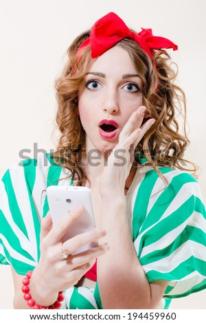 closeup portrait of shocked holding mobile cell phone pinup girl beautiful blond with blue eyes young woman with red ribbon on her head looking at camera on white isolated background image - stock photo