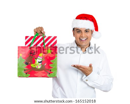 Closeup portrait of shopping smiling excited young handsome man wearing red santa claus hat holding, pointing showing a festive bag, isolated on white background - stock photo